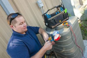 technician with tools and tool bag inspecting the outside unit of an air conditioner
