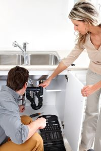woman showing plumber what's wrong with her drain pipe