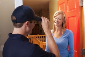 female homeowner greeting plumber at front door