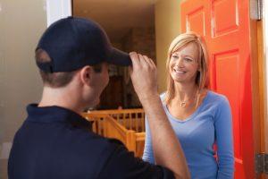 female homeowner greeting plumber at front door
