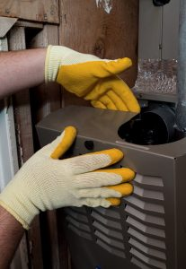 technicians gloved hands repairing heater