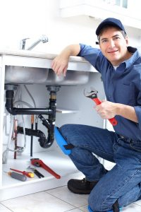 plumber working on plumbing system under sink