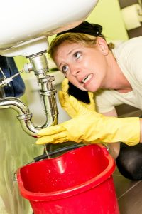 homeowner on phone inspecting leak underneath sink