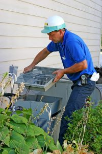 male technician working on outside AC unit