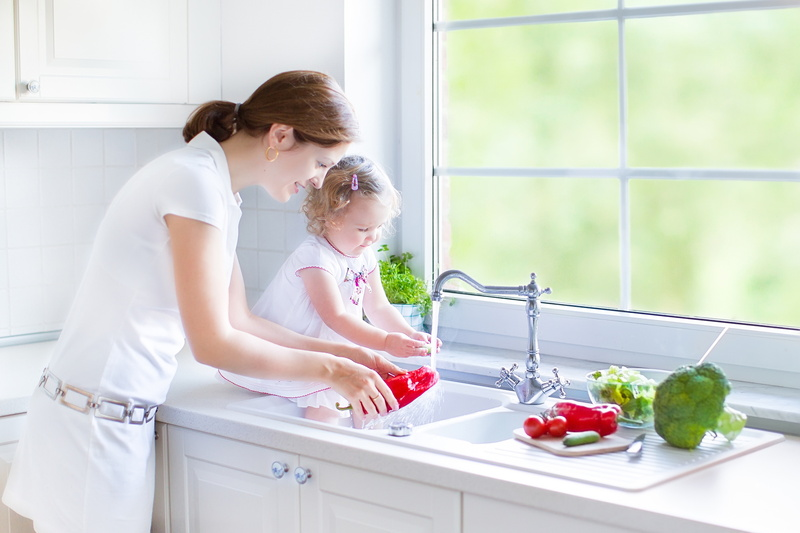 family-standing-over-kitchen-sink