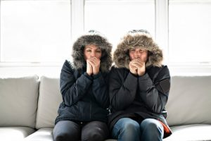 couple-sitting-on-couch-shivering-in-jackets