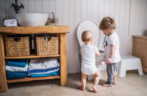 two-small-children-flushing-items-down-toilet