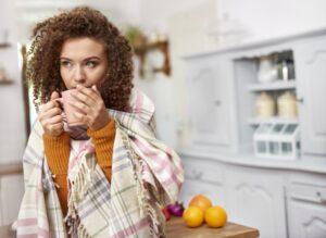 girl-huddled-in-blanket-drinking-out-of-mug